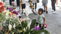 A child lays flowers at Newport Mosque.