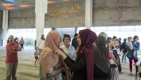 Zainab Badra helps Barbara Hughes of Williamstown put on a hijab at the Newport mosque.