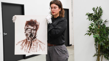 A curator holds Untitled (Concentration Camp) from a series of artworksby Sidney Nolanrelated to the Holocaust.
