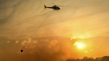 A helicopter water bombs a bushfire threatening homes in Sydney's south-west in April 2018.