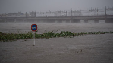 A sign is partially submerged as the Tama River floods.