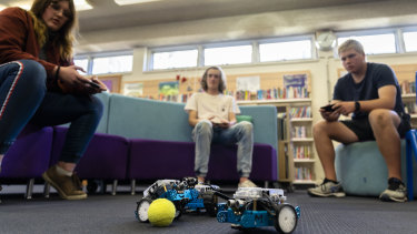 Alfred Deakin High School Year 10 students Shanti Geoghegan (left), Tom Hilton, and Liam Ayres play a game of soccer with their phone operated robots.