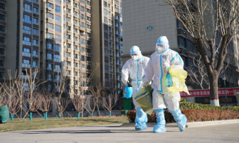 Workers carry a container of coronavirus test samples outside of a residential neighbourhood in Shijiazhuang in northern China's Hebei Province on Friday.