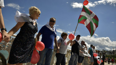 The Basque flag flies among those gathered at La Concha beach to demonstrate for independence as part of a 200-kilometre human chain.