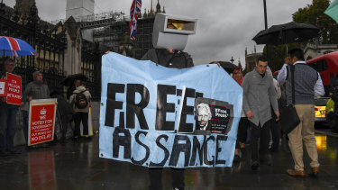 A supporter of Julian Assange protests outside the Houses of Parliament.