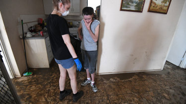 Sue Pollard (right) is comforted by her daughter inside her flood-affected house in the Townsville suburb of Hermit Park.