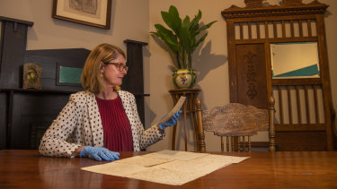 Curator Elise Edmonds holding some letters from the Burrowes' children in a recreation of the Burrowes' family home in Rooty Hill.