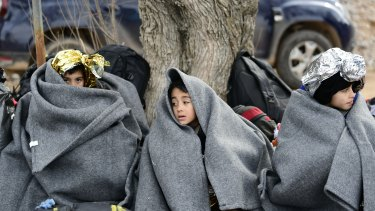 Children from Afghanistan use blankets to warm themselves after an arrival of a dinghy at the village of Skala Sikaminias, on the Greek island of Lesbos, after crossing the Aegean sea from Turkey.