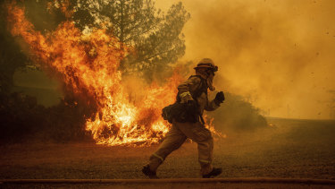 A firefighter runs while trying to save a home as a wildfire tears through Lakeport, California.