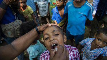 A child in Papua New Guinea receives a polio vaccine. The coronavirus outbreak threatens to reverse decades of global progress in alleviating poverty.