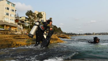 Madelaine Langley and Derrick Cruz climb into Cabbage Tree Bay to monitor crayweed.