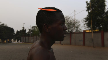 A soccer player at the end of a game on the streets.