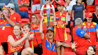Good as gold: Suns fans cheer on their team at Metricon Stadium.
