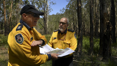 RFS District Officers Steve Farrell and Stuart Robb inspect a map of the Lindfield Park Road fire, which has been burning since last July.