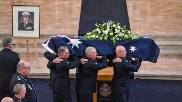Former chief commissioner Mick Miller's coffin is carried out after his funeral.