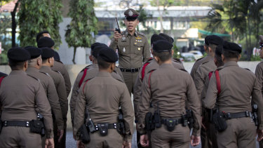 A police officer briefs others outside a polling station before the start of voting in Bangkok, Thailand, on Sunday.