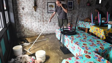 Ben Coles cleans up his restaurant in Narrabeen after Sunday's flooding.