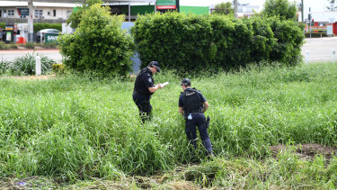 Police examine the scene where two bodies were found in a drain behind the Aitkenvale Library in Townsville.