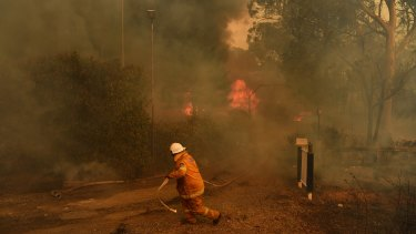 A RFS firefighter in front of a house that could not be saved from fire on Thursday on the outskirts of Bargo.
