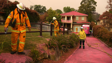 Firefighters clean up in Turramurra after fire retardant was dropped from a plane on Tuesday.