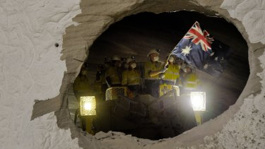 A worker on one of the two roadheaders waves the Australian flag moments after smashing through sandstone connecting two sections of the M4-M5 Link.