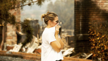 A woman, who declined to give her name, surveys damage to her grandmother's house in Redding.