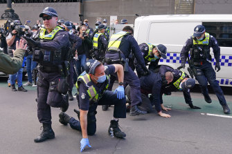 Police officers detain a man as protesters gather outside Victoria's Parliament House on Sunday.