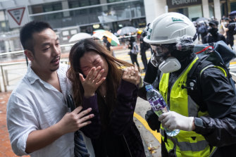 A first aid volunteer assists a pedestrian affected by tear gas during a protest on Queensway.