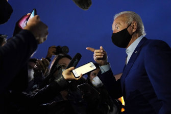 Democratic presidential candidate  Joe Biden speaks with reporters before boarding a plane at an airport in Detroit.