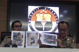 Indonesian National Police spokesperson Brigadier General Dedi Prasetyo, right, and an aide show photos of items confiscated during anti-terror raids.