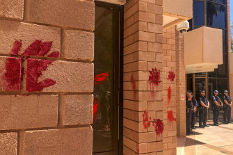 Protesters leave red hand prints outside the Alice Springs police station following the death.