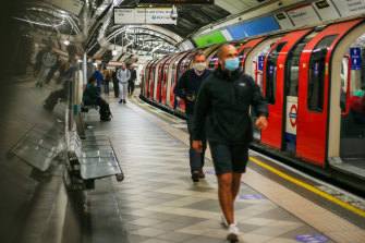 Commuters in masks walk along a platform at Bank station on the London Underground.
