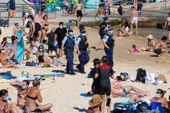 Masked police amid the unmasked crowds on Bondi Beach last Sunday.