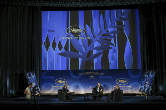 Cannes Festival director Thierry Fremaux, centre, festival president Pierre Lescure, right, and journalist Laurent Weil talk during the presentation of the festival line-up, in an empty cinema in France on Wednesday.