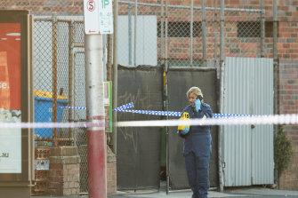 Police at a tram stop in Kew where a man was stabbed to death.
