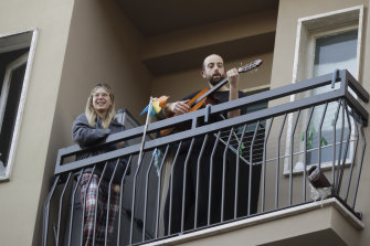 "A man in Milan plays guitar on the balcony of his home as part of a flash ""non-mob"" launched throughout Italy to help people cope with being in lockdown."