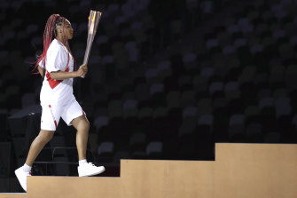 Naomi Osaka carries the Olympic torch during the Tokyo Games opening ceremony.