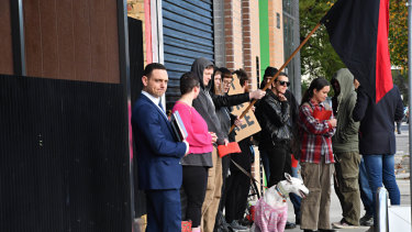 A real estate agent holds an open for inspection at Melbourne Anarchist Club as members protest the sale of the building.