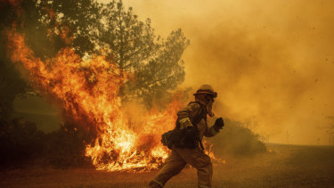 Some jobs present significantly higher risks to life. A firefighter runs while trying to save a home as a wildfire tears through Lakeport, California.