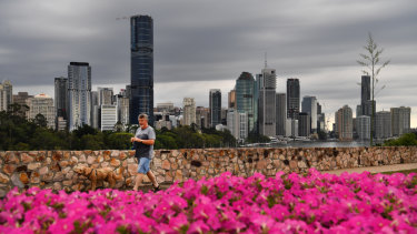 A  man is seen walking his dog at the Kangaroo Point cliffs as storm clouds gather over the Brisbane CBD.