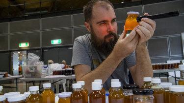 Dr Tobias Smith shines a light through the honey to test its clarity at the Royal Easter Show's native honey competition.