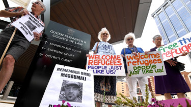 Placards are held at a vigil outside the Brisbane Magistrates Court on Monday.