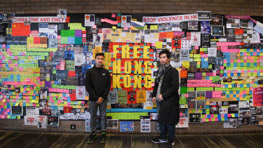 "Two pro-democracy protesters stand in front of a ""Lennon Wall"" at the University of Technology Sydney."