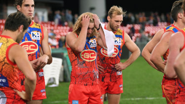 Suns players after their loss to Adelaide at Metricon Stadium.