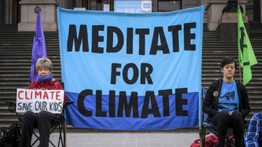 Protesters meditate for climate change action on the steps of Parliament on Monday.