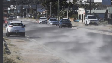 Sand is blown down Prince Charles Parade in Kurnell as winds made conditions uncomfortably cool for many on Friday.