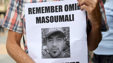 A photograph of Omid Masoumali is held outside the Brisbane Magistrates Court in Brisbane.
