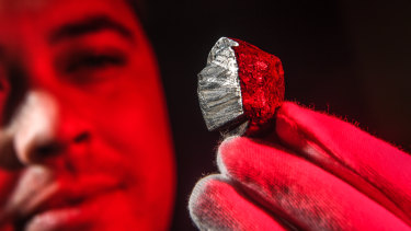 Dr Stuart Mills with the Wedderburn meteorite. Scientists have discovered a new mineral buried inside it, forged in the core of a planet that no longer exists.