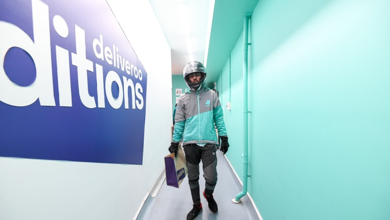 A delivery rider takes an order from Deliveroo's dark kitchen in Windsor.