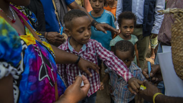 A boy's finger is marked with black after a Polio vaccination.